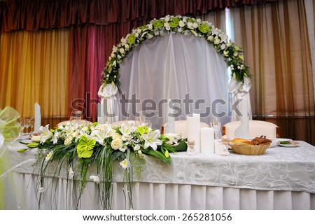 White bouquet of flowers on a festive table bride and groom in a restaurant - stock photo