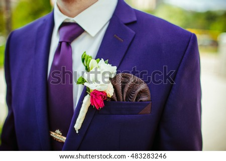 White boutonniere pinned to blue man's jacket with brown napkin