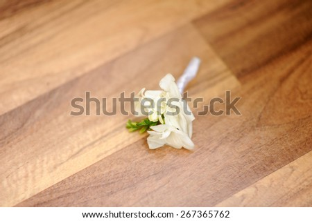white boutonniereon the wooden floor - stock photo