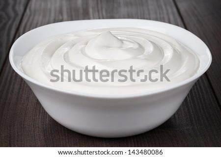 white bowl full of sour cream on wooden table - stock photo