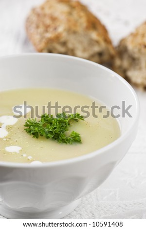 White bowl of asparagus soup with chervil and drops of cream. Grainy bread on background. Healthy food. - stock photo