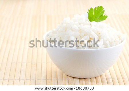 white bowl of boil chinese rice over bamboo - stock photo