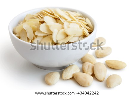 White bowl of peeled flaked almonds on white. Spilled whole almonds.