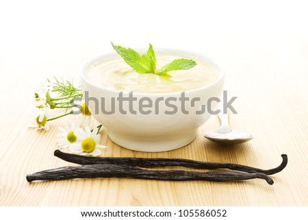 White bowl of vanilla yogurt with vanilla beans, flowers and a spoon on wood - stock photo
