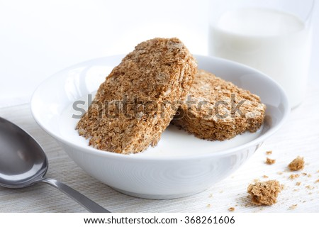 White bowl with two whole wheat breakfast biscuits isolated on white with milk, bottle and spoon. Crumbs on placemat.