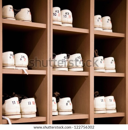 White bowling shoes on racks - stock photo