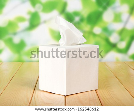 White box with napkins against green foliage - stock photo