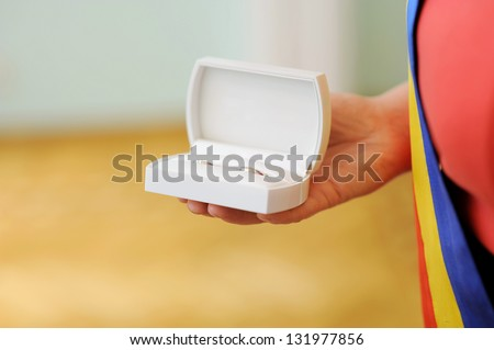 white box with wedding rings in hand - stock photo
