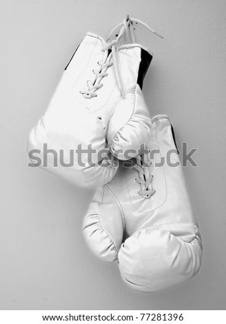 White boxe gloves pending from a nail on a wall - stock photo