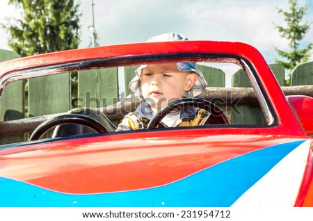 White boy playing in the car rocker - stock photo