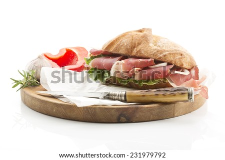 White bread with ham from South-Tirol bell pepper lettuce garlic served on wooden board - stock photo