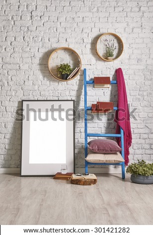 white brick wall interior with ladder and frame decor - stock photo