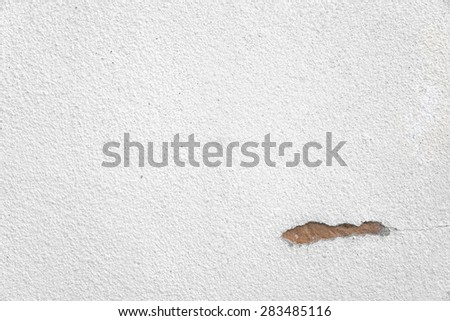 White brick wall with small crack showing orange brick within the wall - stock photo