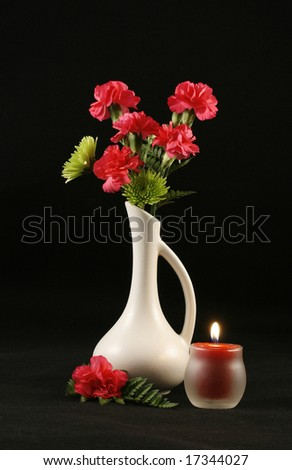 White bud vase with pink carnations, candle over a black back drop with room for copy.