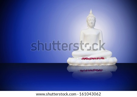 White Buddha ornament isolated against a drack blue background - stock photo