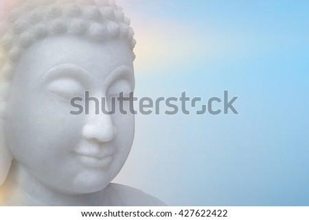 White Buddha portrait isolated on light blue background. - stock photo