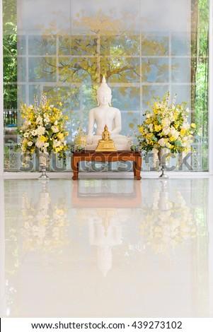 white buddha with golden buddha on wood table  - stock photo