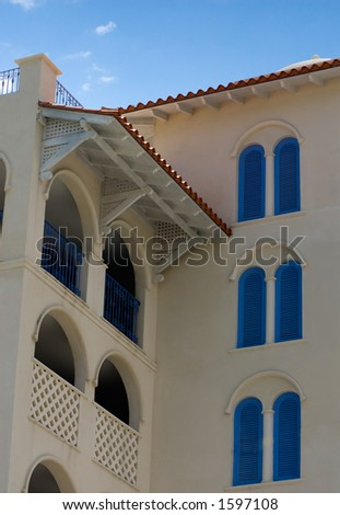 White building in Barbados with bright blue trim and shutters. - stock photo