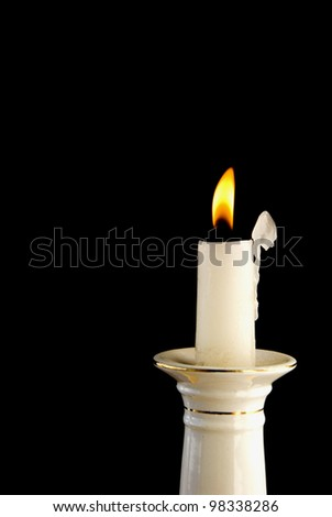 White burning candle in candlestick in the dark background - stock photo