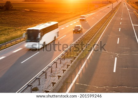 White bus in motion blur on highway at sunset - stock photo