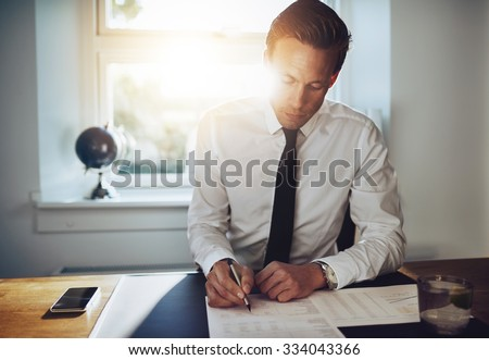 White business man signing a contract and looking at documents at his office while looking serious - stock photo