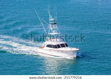White cabin cruiser speeding across blue water in harbor - stock photo
