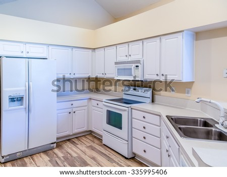 White cabinets and appliances with a new hardwood floor in a kitchen - stock photo