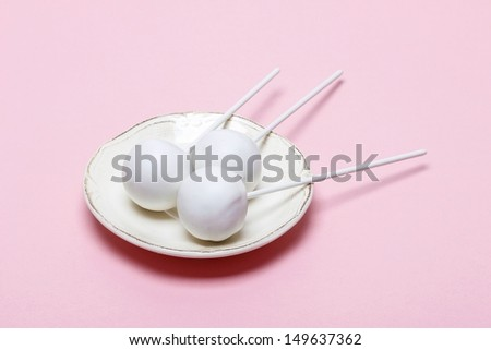 White cake pops on pink background. Copy space - stock photo