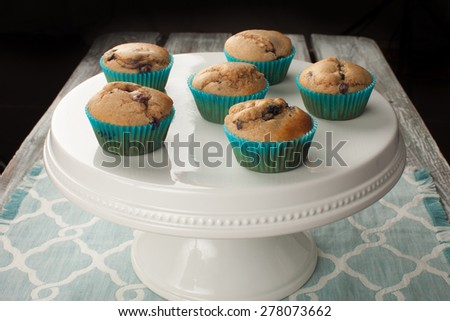 white cake stand with fresh homemade blueberry whole wheat muffins on a blue and white place mat with a black background - stock photo