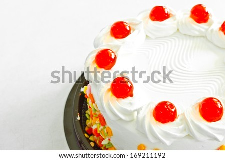 white cake with artificial cherry