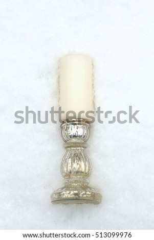 White candle and candlestick glass vintage in the snow. Top view flat lay. Vertical shot