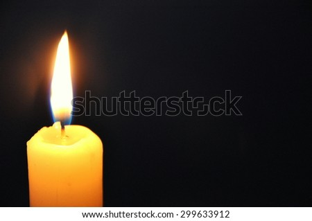White candle burning in the dark - stock photo