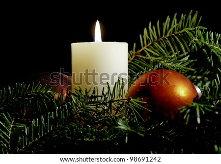 White candle surrounded by red Christmas balls and evergreen branches with black background. - stock photo