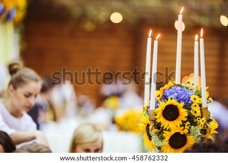 White candles burn standing in the yellow bouquet