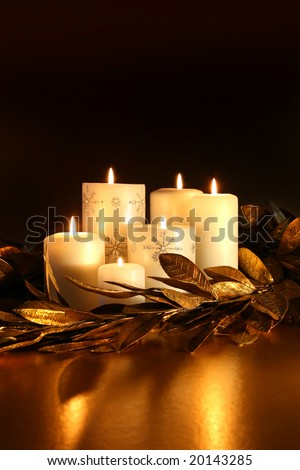 White candles with gold leaf garland on dark background - stock photo