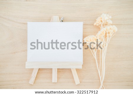 White canvas art board on wood texture background with dried flower - stock photo