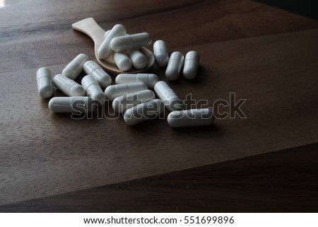 White Capsule Pills on wooden table and spoon