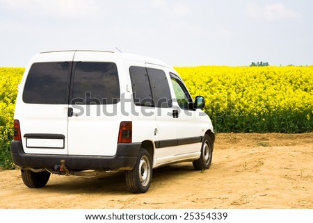 white car, with yellow field - stock photo