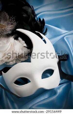 white carnival mask on blue silk - stock photo