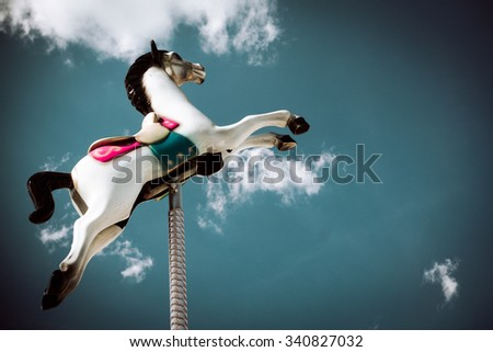 white carousel horse jump in the blue sky