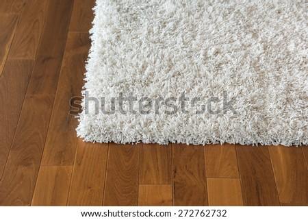 white carpet on parquet floor - stock photo