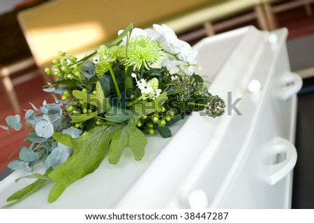 white casket with flowers - stock photo