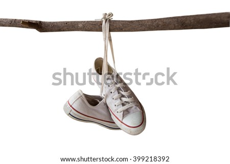 white casual shoes hanging on branches. isolated with clipping paths - stock photo