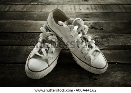 white casual shoes on wood background