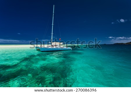 White catamaran in shallow tropical water with green snorkeling reef - stock photo