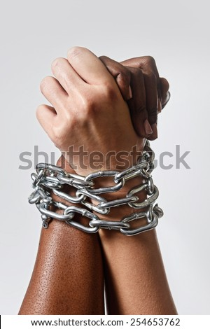 white Caucasian hand chained with iron chain and locked together with black ethnicity female around wrists in togetherness, multiracial respect and understanding concept isolated on even background - stock photo