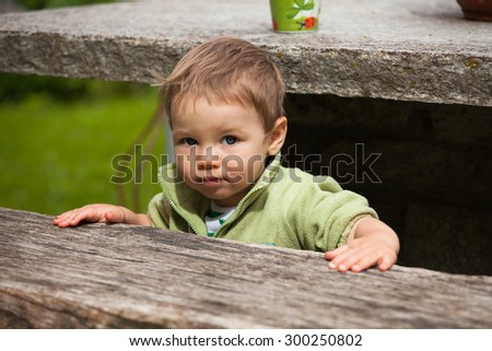White Caucasian light haired sad one year old baby boy tries to hide under the stone table while holding the wooden bench - stock photo