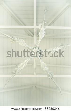 White ceiling fan on a white ceiling, with white boards - stock photo