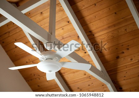 White ceiling fan on exposed support stock photo royalty free white ceiling fan on an exposed support beam with a vaulted wood ceiling in mozeypictures Choice Image
