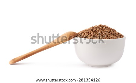 White ceramic bowl full of the buckwheat seeds and wooden spoon next to it, composition isolated over the white background - stock photo